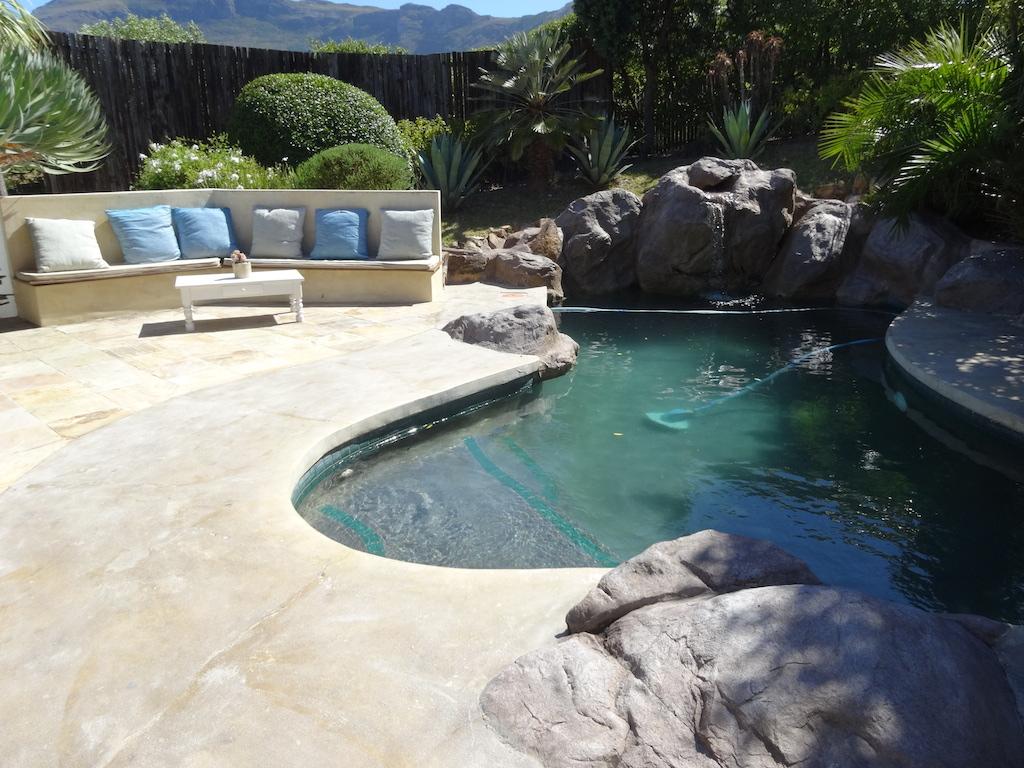 Het zwembad en de tuin van bed and breakfast African Queen